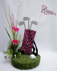 We had fun designing this Pink Leopard covered styrofoam golf bag themed centerpiece. Our circular base is covered in spanish moss to represent golf greens. We have a golf ball situated as though i...