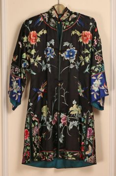 China, lady's black embroidered informal coat, decorated with birds, butterflies, and floral motifs, the arms with blue cuffs, early 20th century