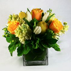Billy Balls, Canary Yellow Roses, Scented Geranium Leaf, and Fresh Lemons. Nothing is more cheery than these crisp, bright yellows and cream... square vase