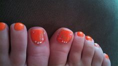 Orange toe nails with a cute design