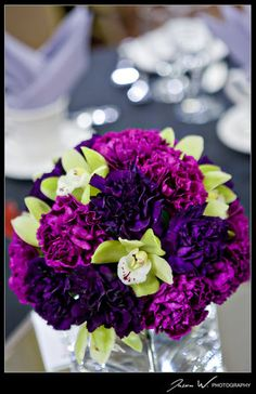 purple and green centerpiece of carnations and orchids