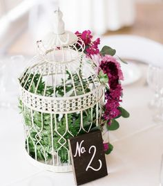 Early Spring Wedding // Pink  | Wedding centerpiece idea: vintage birdcage filled with ferns and accented with a spray of pink blossoms. A handwritten table number adds to the charm.    Venue: On Sunny Slope Farm | Photographer: The Mallorys