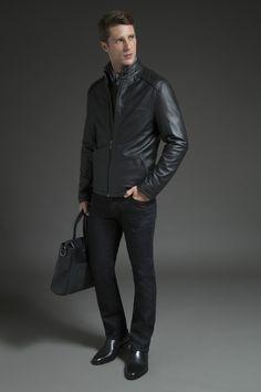 Camisa listrada casual sobreposta por tricô cinza com zíper frontal e jaqueta preta de couro com texturas. A calça jeans, a chelsea boot e a pasta messenger finalizam a produção dark com elegância.