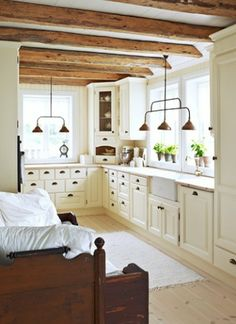 Love the white cabinets and rustic beams!