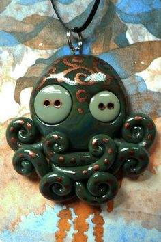 An octopus made with polymer clay and button eyes.  The bronze details are acrylic paint.