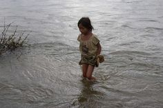 Young girl standing in the Mekong River.  Every 8 seconds a child dies from drinking contaminated water (that's 10,000 a day!)