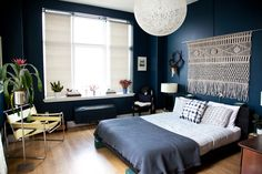In contrast to the white, bright look of the rest of the home, shades of blue are layered throughout the master bedroom. A custom macrame piece above the bed acts as an alternative headboard and stands out againstthe navy walls. The bedding is from ABC Carpet & Home.