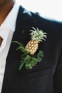 a black suit, a white shirt and a pineapple boutonniere