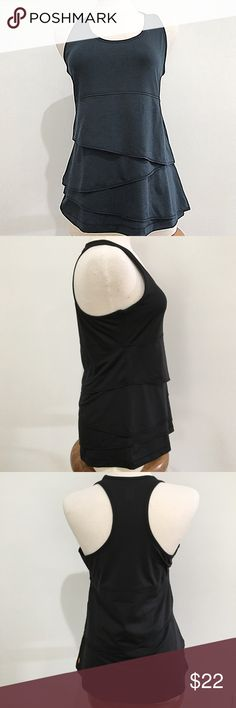 Lucy fitness black racerback tank with ruffles L Live each day with passion! This cute tank will help get you to your next goal by bringing you a little extra joy with each step. The layered material adds a unique feminine touch to your workouts and does not cling to your waistline. Material tag missing but most probably poly/spandex blend. Approximately measures flat across: bust:18, length:27. Great condition! Lucy Tops Tank Tops