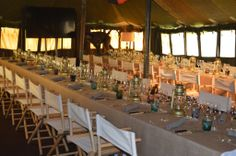 The parrafin lamps and canvas chairs add an authentic bush feel to this safari theme tent.
