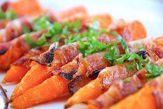 Her får du opskriften på gulerødder med bacon, der er små snackgulerødder omviklet med baconskiver og penslet med honning.  Gulerødder med bacon er ikke alene nemt at lave, det er altså også smukt tilbehør, som de