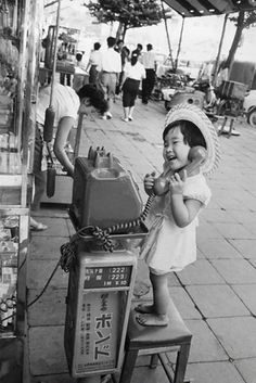 A little girl having fun pretending to talk on the... - Historical Times