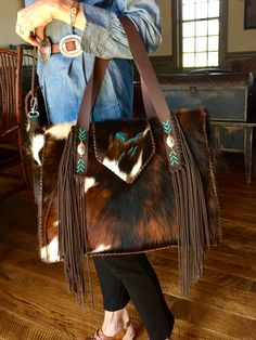 The Buckaroo Tote, with vintage sterling silver conchos and side fringe on the straps, side pockets lined in suede, and a turquoise running horse on the flap. gowestdesigns.us