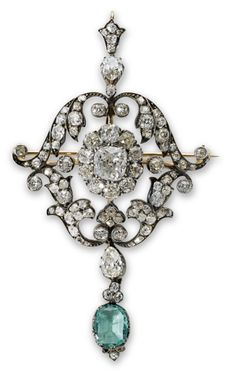 An antique emerald and diamond pendant brooch.The cushion-shaped diamond within an old-cut diamond cluster set to the centre of a similarly cut diamond foliate frame and pendant bail, terminating in a pear-shaped diamond and oval mixed-cut emerald drop, mounted in silver and gold.