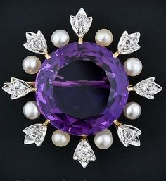 A brooch with a sumptuous royal purple amethyst bursting with twinkling diamond leaves and shimmering pearls. Signed by the pioneering American Jeweler Black Starr & Frost. Circa 1900.