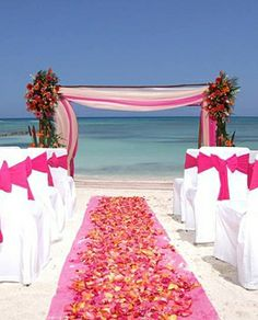 Out of everything ive found, this would be perfect!! Bebe'!!! Lovely draped pink fabric archway with flowers in all shades of pink!!! Perfect for a pink beach wedding!!!