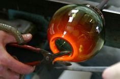 """""""Hot glass is cut off the open end with a special pair of shears to give the finished bowl an even rim."""" slyglass by Steve and Léona Lindars"""
