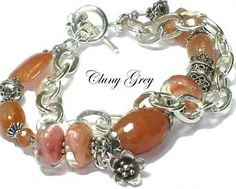 a bracelet made with peach aventurine and boro lampwork beads with a heavy sterling silver chain and sterling charms - #bracelet  #unusualjewelry  #jewelry