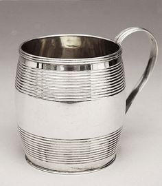 A Georgian silver Christening mug, in the shape of a barrel, decorated with reeded bands. The interior is gilt, and the handle is also decorated with reeded bands. This type of Christening mug was popular between 1800 and 1820 (Waldron, Price Guide to Antique Silver, pg 190). The hallmarks are clear with the exception of the makers mark, which is only partially visible. The first letter T is clear, but the second letter is worn (could be D, P or R).