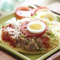 Honduran Enchiladas These are not regular enchiladas. Made in the style of a tostada, golden fried corn tortillas, topped with a combination of ground meat, egg, cheese, tomatoes, and cabbage a favorite appetizer.