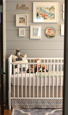 Gallery wall above crib. Love the gray paneled walls!