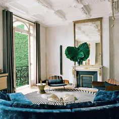 How beautiful is this Parisian apartment by Studio KO? // #paris #parisapartment #parisliving #parisiandesign #oldmeetsnew #traditionalarchitecture #moderndesign #deepteal #curvedsofa #designinspiration #colorinspiration #interiordesign #interiordesigner #palms #fireplace #mantle #sofa #chairs #loungechairs #brazilianmodern #jorgezalszupin #studioko #livingroom #livingroomdesign