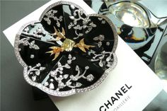Camélia Coromandel brooch by Chanel Jewelry in 18 carat white gold, white and yellows diamonds, and black enamel.