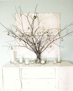 Great use of all the twigs in my backyard. Branches in the largest vases and hang christmas balls from them. need ornament hangers.