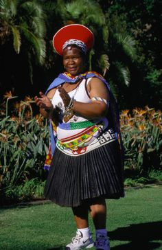 A Zulu lady wearing a traditional isicholo (wide hat decorated with beads), performs a dance at the Botanical Gardens.