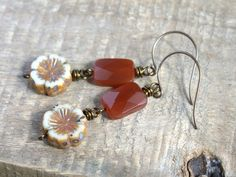 Carnelian Gemstone Earrings with Czech Glass Flower Beads. Rustic  Flower Earrings. Wire Wrapped Boho Jewelry.-- -These earrings feature opaque cream Czech glass pansy flower beads. The flowers have a rustic terracotta Picasso finish around the edges and in their carved centre. Wire wrapped above are faceted Carnelian gemstone rectangles, which really sparkle and catch the light beautifully. Round Vintaj brass earwires and measure about 6 1/2 cm in total.