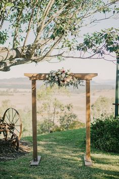 Simple rustic country outdoor wedding ceremony with wooden arbour and flowers   Sophie Baker Photography