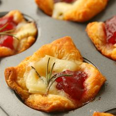 Cranberry Brie Bites are a super easy but beautiful appetizer. Made with crescent roll dough, brie, whole cranberry sauce and a sprig of rosemary!