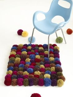 Pom-Pom Rug - Make 10 rows of 12 Pom-Poms each on canvas, arranging colors as desired. With large-eyed blunt needle and matching yarn, sew Pom-Poms to canvas. Weave in ends.