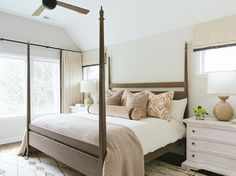 Neutral bedroom features a brown 4 poster bed dressed in pink and brown pillows as well as a pink and brown velvet bolster pillow flanked by whitewashed nightstands and brown lamps, Aerin Gannet Lamps, placed under windows dressed in cream roman shades.  Kate Marker Interiors