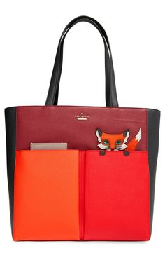 Falling in love with the playful fox peering out from the pocket of a this color-blocked, leather tote from Kate Spade.