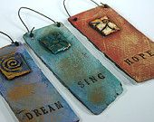 Lisa Wolters clay work.  Artist from Yellow Springs, Ohio (local artist enclave).  These are the smallest pieces with single words: Faith, Love, Dream, Sing, Dance, Namaste, Hope, Believe.  Large piece have full quotes from Jack Sparrow, Paul Neruda, Lao Tzu, Emily Bronte, Van Gogh, Einstein, Grandma Moses, Oscar Wilde, and the list grows.