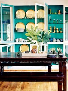 A wall of built-ins keeps everything close at hand, and benches accommodate intimate dinners or raucous parties. Saturated turquoise showcases gold tableware.