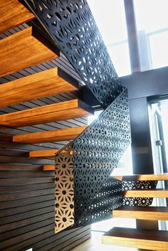 Laser cut metal screens have been used here as stair railing - a simple idea that's both eye catching and practical. I love the way the light pours through, illuminating the pattern.: