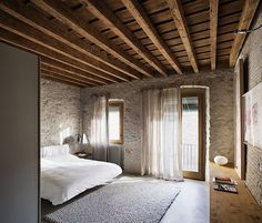 Masculine bedroom with wooden rafters, white bed, stone like walls, French doors, sheer white curtains and grey carpet. Simple lines, large and open. Lovely.