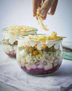 Sałatka z warstwami śledzia, cebuli, ogórków konserwowych, ziemniaków gotowanych w mundurkach, kolejnej warstwy majonezu i pieprzu, tartego, gotowanego buraka, zwieńczona majonezem, pieprzem i…