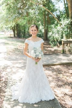 Beautiful classic bride with white and pale blue flowers and lace dress