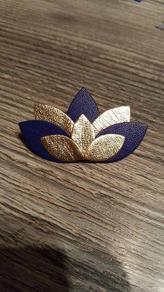 Broche en cuir. Modèle lotus. 5 grands petales et 3 petits. 2 coloris : bleu nuit et doré. Attaché dorée. Possibilité de personnaliser votre commande. Nhésitez pas à me contacter.