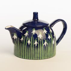 Snowdrop Teapot with a deep blue background and a row of snowdrops all around it. Hand painted by Hannah Berridge.