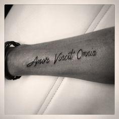 Amor vincit omnia tattoo text wrist