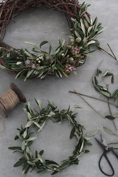 Beautiful Olive branch wreath created by Norwegian stylist, Elisabeth Heier. A different  use of tree branches to decorate. For the top wreath she attached the olive leaves to a grapevine base using thread and then added pine cones and flowers. The bottom wreath is made like a wreath crown (check the site for instructions in Norwegian) Simple and elegant.