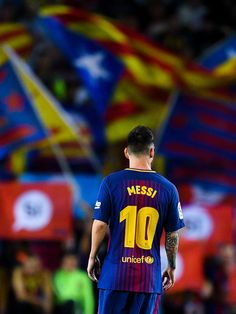 Lionel Messi of FC Barcelona looks on as Catalan Pro-Independence flags are seen on the background during the La Liga match between Barcelona and SD Eibar at Camp Nou on September 19, 2017 in Barcelona.