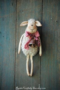 I made this little sheep of cotton and wool and stuffed it with poly fiberfill. She has been stained with coffee and cinnamon grunge. She has beads for eyes. She wears a red and white checked bow and a rusty bell.  This cute primitive sheep would make a wonderful rustic country house or farmhouse décor. She measures approximately 8 x 3 inches, 20x7cm. She has a loop behind for hanging.  This is my own design. This doll is decorative and is not suitable for kids as some of his features and…