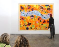 """Visitors viewing Merion Estes' """"Cooling Trend"""" in our project room. . http://ift.tt/2iTReC6 . After experiencing yet another hottest summer on record Estes wanted to somehow depict that in a painting. Starting with the most extreme orange-yellow color hot spots and sunrays she added blooming flowers and visual symbols of after-effects experienced by viewing the sun while outdoors. The cool passage in the center offers a respite to the eye and psyche while also referring to a giant brush…"""