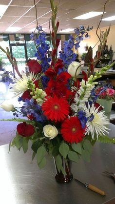 Red, White and Blue Flowers---just in time for July Gerbera Daisy, Blue Delphinium, Roses, Gla Altar Flowers, Church Flowers, Beautiful Flower Arrangements, Funeral Flowers, Wedding Flower Arrangements, Floral Arrangement, July Flowers, Summer Flowers, Fresh Flowers