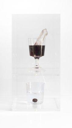 (2015) Summer Wine : Gabriel Leger Dans une boîte de plexiglas à deux étages, ont été placés deux verres contenant chacun un liquide et un minéral brut.  À l'étage du dessus, une pointe de cristal de roche trempe dans un verre  à vin, rempli de vin rouge. Exactement en-dessous, un grenat baigne (mais semble y flotter) au milieu d'un verre à eau.  Ces verres sont les vestiges d'un entretien entre deux personnes, l'une ayant bu du vin l'autre de l'eau. Depuis, des pierres symboliques de…